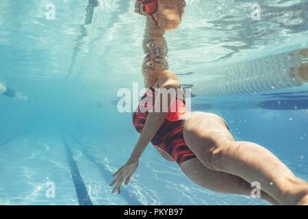 Underwater nageuse en action à l'intérieur de la piscine. Mettre en place les jeunes femmes formation nageur dans la piscine. Banque D'Images