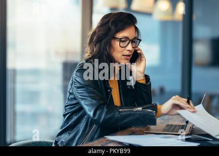Asian Business Woman talking on cell phone tout en travaillant au bureau. La lecture de certains documents cadres féminins et talking on mobile phone. Banque D'Images