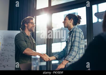 Young businessman shaking hands with collègue masculin après réunion en salle du Conseil. Après poignée de réunion réussie. Banque D'Images