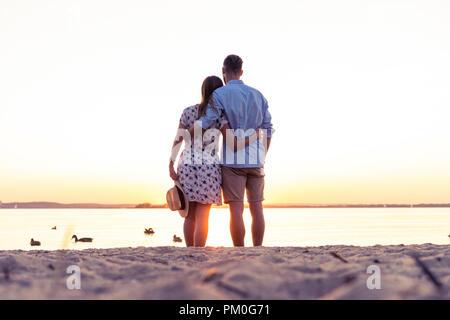 Couple en train de marcher sur la plage au coucher du soleil Banque D'Images