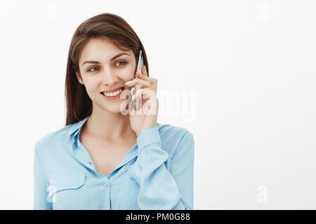 Mère Fille appelant au travail. Portrait of positive heureux mignon femelle collègue en blouse bleue, holding smartphone nouvelle oreille, regardant de côté et sourire, parler avec tes amis et profiter de la conversation de nice Banque D'Images