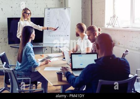 Travailler dur pour gagner. Businesswoman effectuant une présentation d'affaires à l'aide d'un chevalet tout en travaillant dans le bureau de création. Banque D'Images