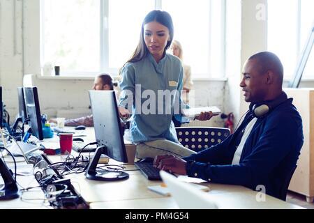 Dure journée de travail. Vue supérieure de jeunes gens modernes dans smart casual wear discuter affaires alors qu'il était assis dans le bureau de création. Banque D'Images