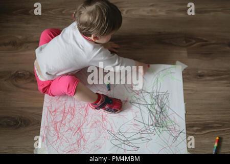 Une petite fille dessine avec des crayons de couleur sur une grande feuille blanche Banque D'Images