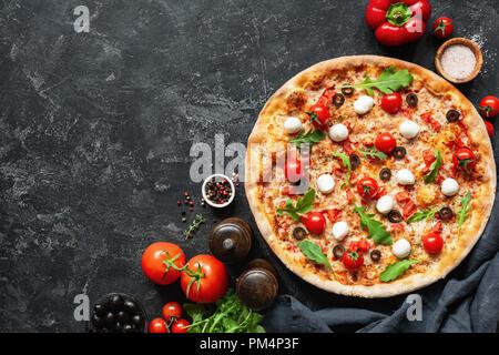 Pizza italienne sur fond de béton noir. L'espace de copie pour le texte. Pizza savoureuse Banque D'Images