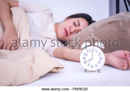 Femme endormie sur le lit avec réveil à 8h00 Banque D'Images