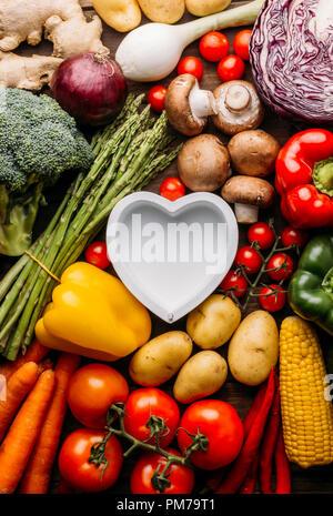 Vue de dessus d'une table en bois plein de légumes et dans le milieu de l'image d'un plat en forme de coeur vide conceptuel, photo, amant de l'alimentation Banque D'Images