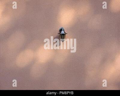 Seule lanterne cuivre brillant se répercute sur le mur texturé ordinaire avec des piscines de lumière pommelé à Seix dans l'Ariège Pyrénées, France Banque D'Images