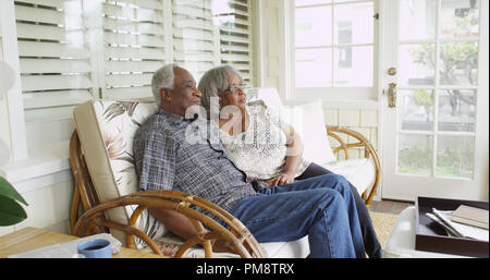 Black mature couple sitting on couch looking away Banque D'Images