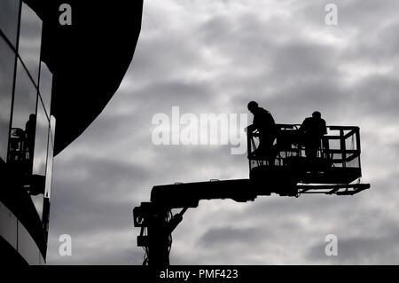 Deux travailleurs de la construction en silhouette contre le ciel gris sur une rampe de levage hydraulique Banque D'Images