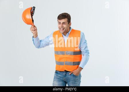 Beau jeune homme ingénieur sur fond blanc le port de casque de sécurité avec sérieux et part choqué avec honte pour erreur, expression de la peur, peur en silence, concept secret Banque D'Images