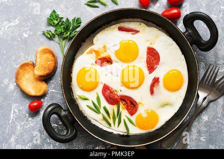 Oeufs au plat avec les tomates dans une poêle, fond gris.Télévision. Banque D'Images