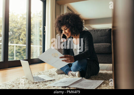Smiling young woman sitting on floor avec peu de rapports talking on cell phone. Femme Africaine à travailler de la maison. Banque D'Images