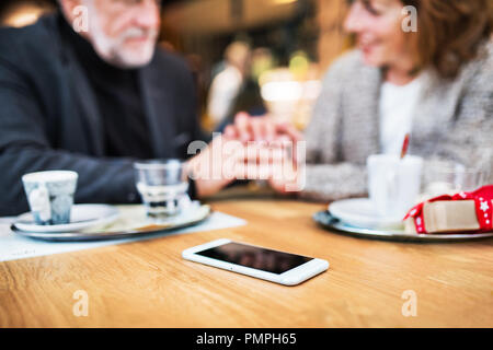 Senior couple with smartphone dans un café, se tenant la main. Centre commercial au moment de Noël. Banque D'Images