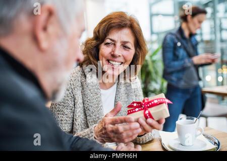 Couple dans un café. Une femme tenant un présent. Centre commercial au moment de Noël. Banque D'Images