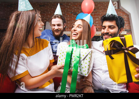 Offrir un cadeau à vos amis femme exceptionnelle dans un party hat, ils sont sourire et rire beaucoup Banque D'Images
