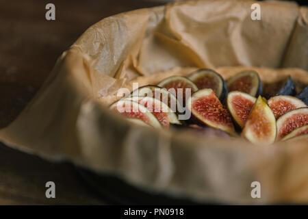 Tranches de figues dans la lèchefrite de papier sulfurisé sur table en bois rustique Banque D'Images
