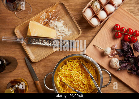 Vue de dessus de spaghetti dans une passoire métallique entouré de divers ingrédients pour les pâtes on wooden table Banque D'Images