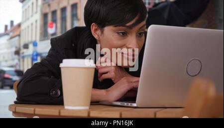 Femme africaine millénaire se lit un e-mail sur l'ordinateur portable à l'extérieur au café en Europe Banque D'Images