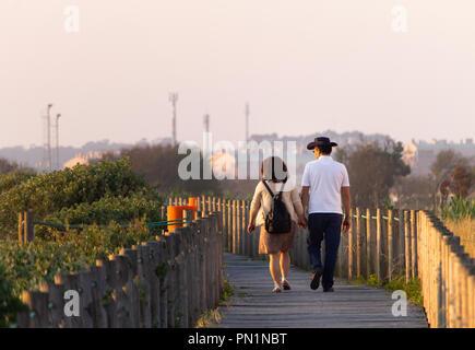 Un couple marche le long d'une allée. Banque D'Images