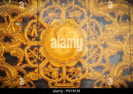 Symbole d'or du Yin - Yang sur le mur de temple Chinois en Thaïlande. Banque D'Images