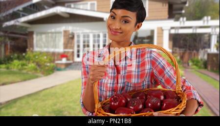 Smiling black female holding panier de fruits à l'extérieur home tossing apple en main Banque D'Images