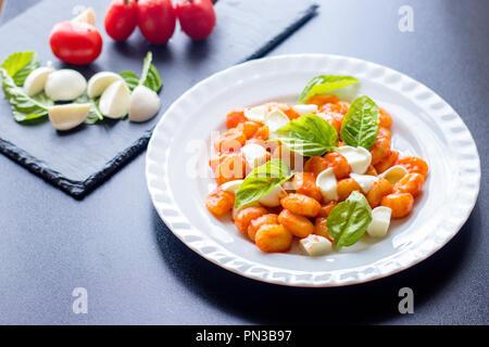 Gnocchi alla Sorrentina en sauce tomate avec basilic frais et vert en tranches de mozzarella balls servi sur une plaque blanche avec des ingrédients sur tableau noir bac Banque D'Images