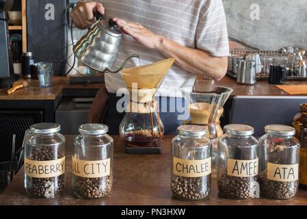 Barista holding pot et verser de l'eau goutte à goutte sur le sol, les grains de café dans le filtre en papier pour préparer le café goutte à goutte dans le café du matin café dri. Banque D'Images