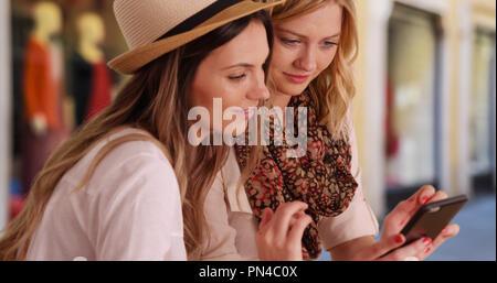 Deux jeunes femmes de partage de médias sociaux près des boutiques de la ville Banque D'Images