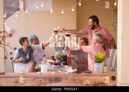 Happy group d'âges différents gens célébrer et s'amuser ensemble dans l'amitié à la maison ou au restaurant. Acclamations et grillage avec cocktails et Banque D'Images