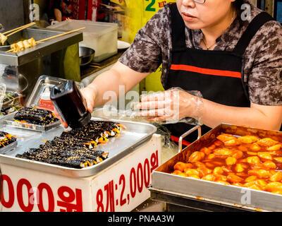 Séoul, Corée du Sud - 21 juin 2017: Femme au service clients au marché de Gwangjang à Séoul. Banque D'Images