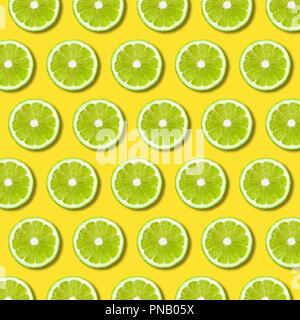 Tranches de lime vert sur fond de couleur jaune vif. La texture des aliments non forfaitaire minime Banque D'Images