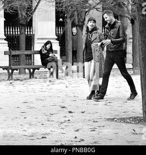 Paris, France. Palais Royal. L'automne, woman sur un banc, young couple walking passé (et un homme effrayant entre les arbres) Banque D'Images