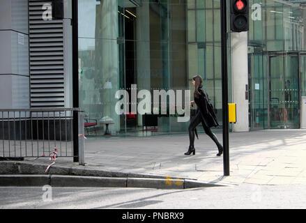 Jeune femme élégante vêtu de noir à marcher le long de la chaussée à l'extérieur d'un corporate Finsbury bâtiment dans la ville de Londres Banque D'Images