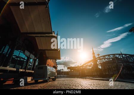 Belle retro style location de paniers sur la place pavée. Arch bridge plus de canaux avec Sankt Katherinen église dans l'arrière-plan. Quartier d'entrepôts à Hambourg, Allemagne. Coucher du soleil chaud de la lumière. De style Renaissance