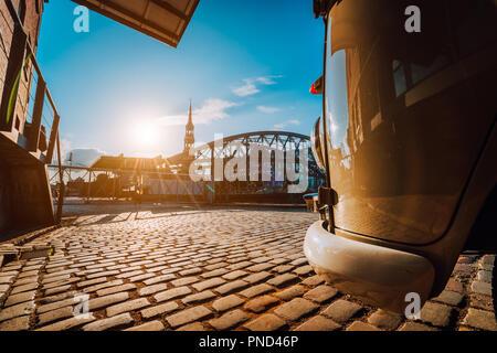 Libre de style rétro voiture sur la place pavée. Arch bridge plus de canaux avec Sankt Katherine église dans l'arrière-plan. De Speicherstadt Hamburg. Coucher du soleil chaud et ciel bleu