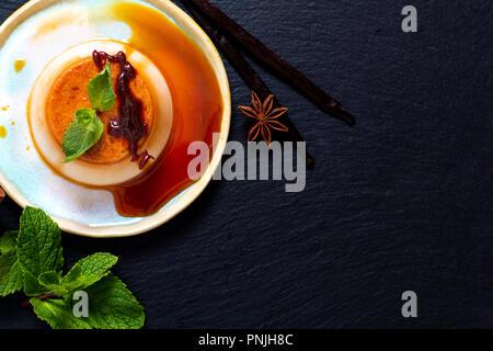 Dessert à la vanille concept alimentaire crème au caramel ou panna cotta aux épices et vanille sur fond noir en noir