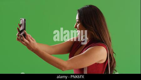 Belle Latina woman using phone de prendre sur un écran vert selfies Banque D'Images