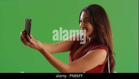 Belle Latina prise femelle selfies sur smartphone écran vert Banque D'Images