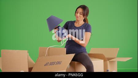 Jeune latina en tenant hors de l'emballage de la lampe lors du déballage sur écran vert Banque D'Images