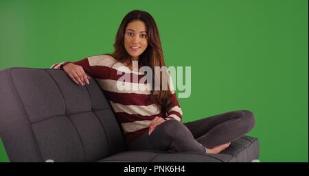 Portrait de belle latine assis sur la table à l'appareil photo sur un écran vert Banque D'Images