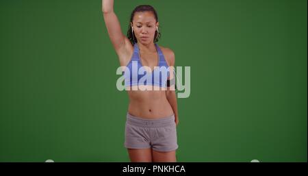 Mettre en place l'athlète femme asiatique qui s'étend sur un écran vert