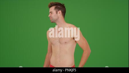 Heureux le type blanc en maillot de standing looking autour sur écran vert Banque D'Images