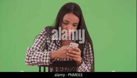Jeune latina assis en arrière dans sa chaise sur son téléphone sur un écran vert Banque D'Images