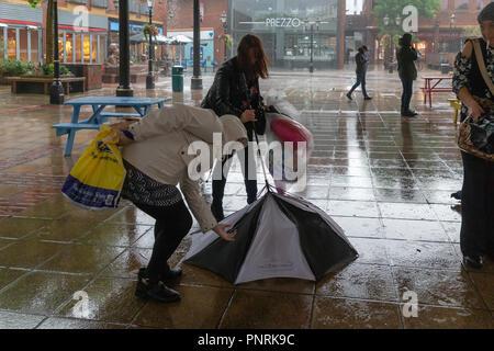 21 septembre 2018 - Les gens luttent pour garder leur parapluie dans le bon sens dans le vent fort. Deux femmes tentent de restaurer leur brolley inversé Banque D'Images