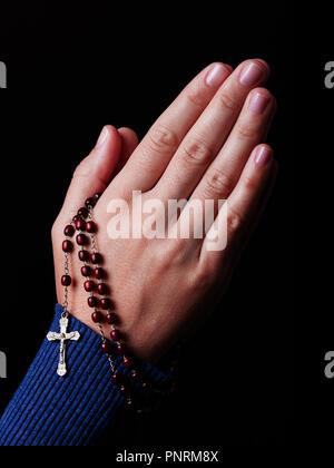 Femme priant mains tenant un chapelet de perles avec Jésus Christ dans la croix ou Crucifix sur fond noir. Femme avec Christian religion Catholique, fa Banque D'Images