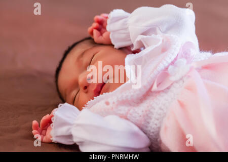 Deux semaines au nouveau-né cute baby girl rose doux vêtements tricotés, dormir paisiblement dans le lit Banque D'Images