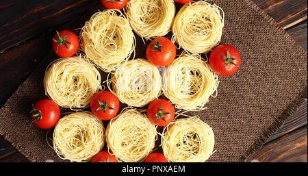 Pâtes alimentaires non cuites et les tomates grappes Banque D'Images
