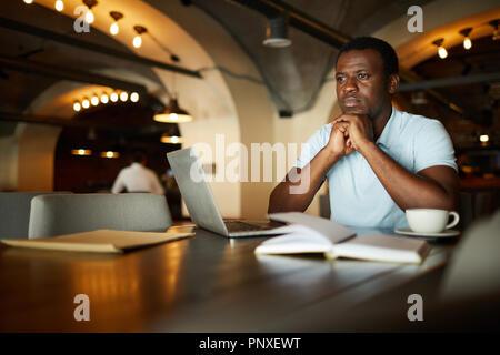 Jeune homme se concentrant sur de nouvelles idées de projet ou de résoudre des points de fonctionnement tout en restant assis dans le café