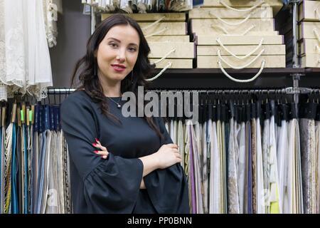 Portrait of happy young woman propriétaire avec bras croisés dans l'intérieur de magasin de tissus, des échantillons de tissu de fond. Accueil Petites entreprises de fabrication de textiles Banque D'Images